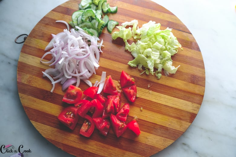 Ingredients to make greek salad are being chopped in wooden board