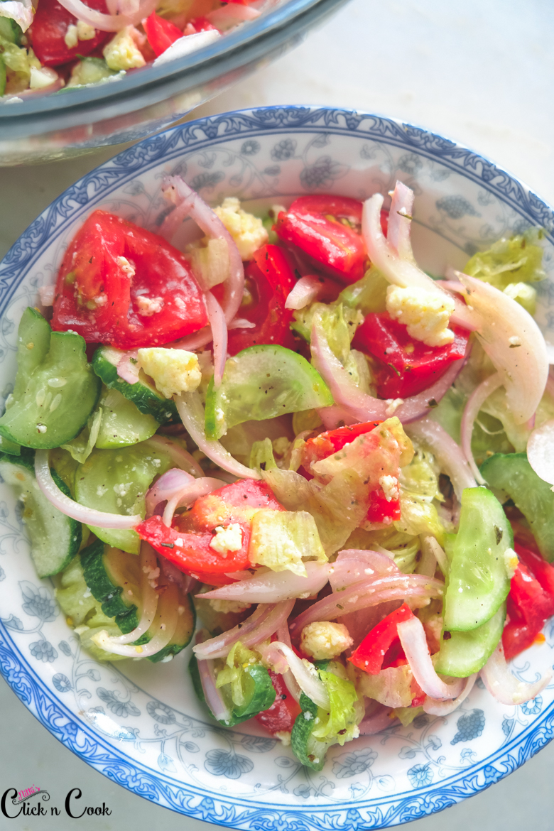 close up shot of greek salad recipe has chopped tomato, onion and cucumber served in small plate