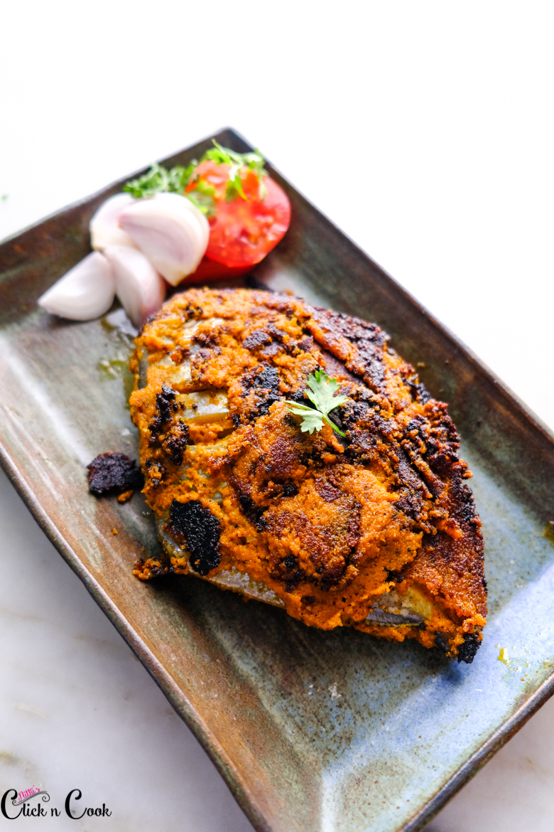 pomfret fry served plate with sliced onion and tomato on sides