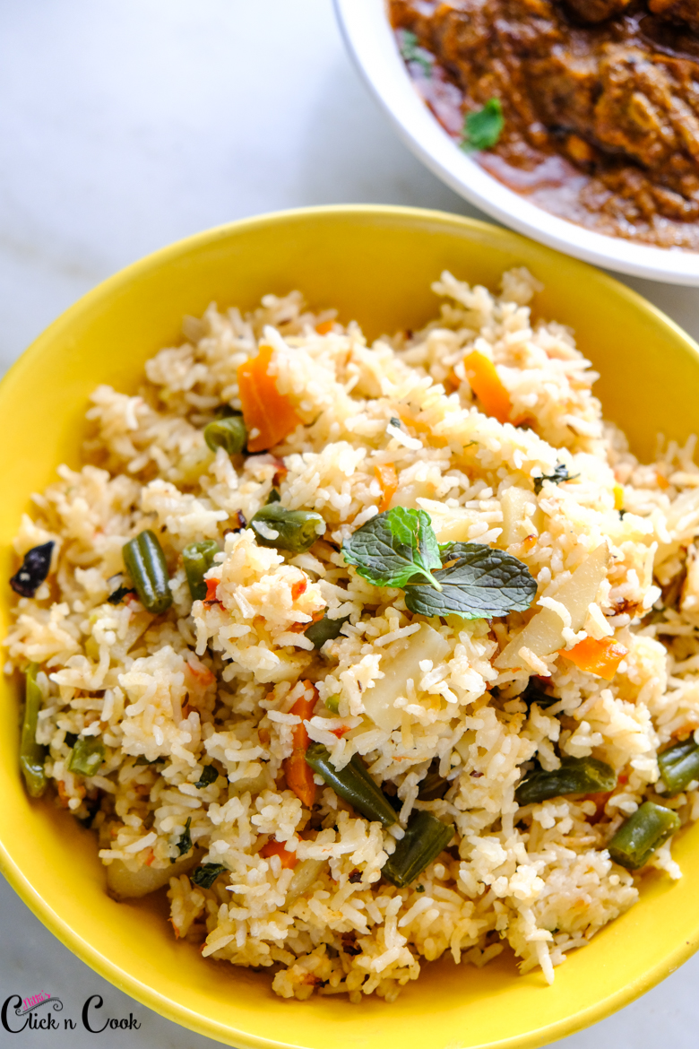 veg pulao recipe is served in yellow bowl with curry aside