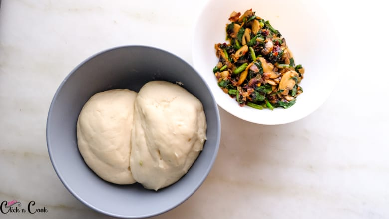 a bowl of dough and another bowl of spinach filling is taken