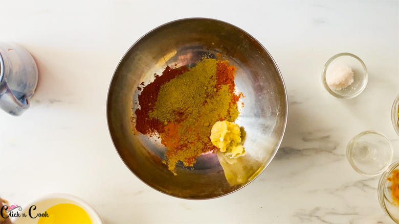 Spice powder, garlic paste are in small steel mixing bowl