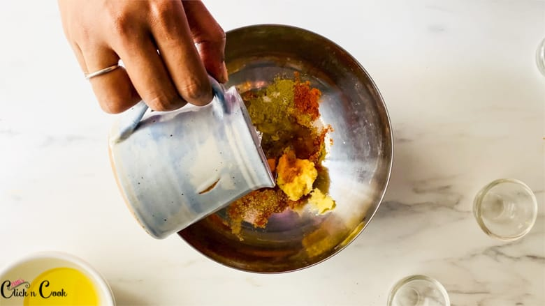 water from the glass cup is being added to a mixing bowl