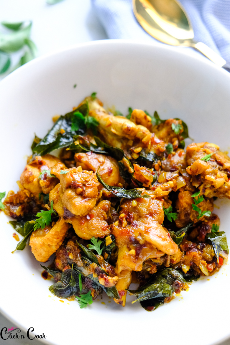 close up shot of gingelly oil chicken served in white bowl
