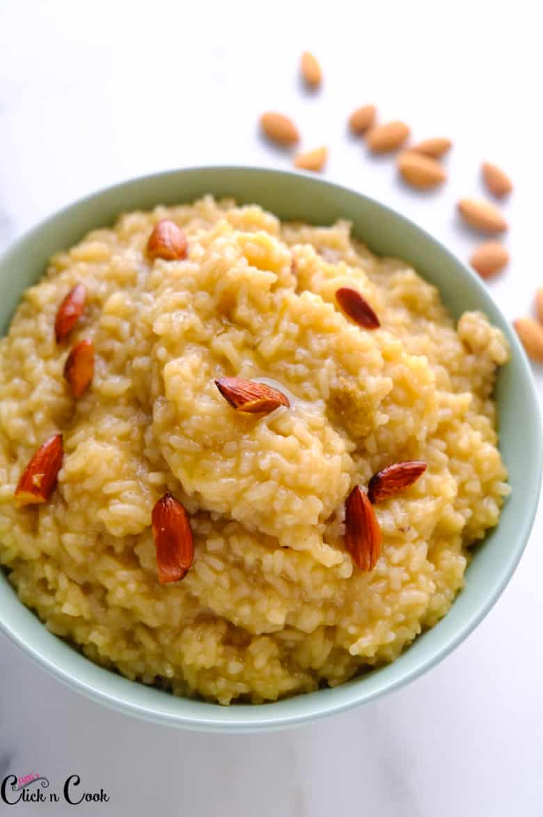 sakkarai pongal served in bowl topped with almonds