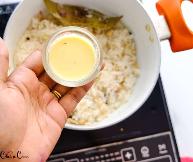 a small glass bowl of saffron infused milk is being added to rice in deep pot