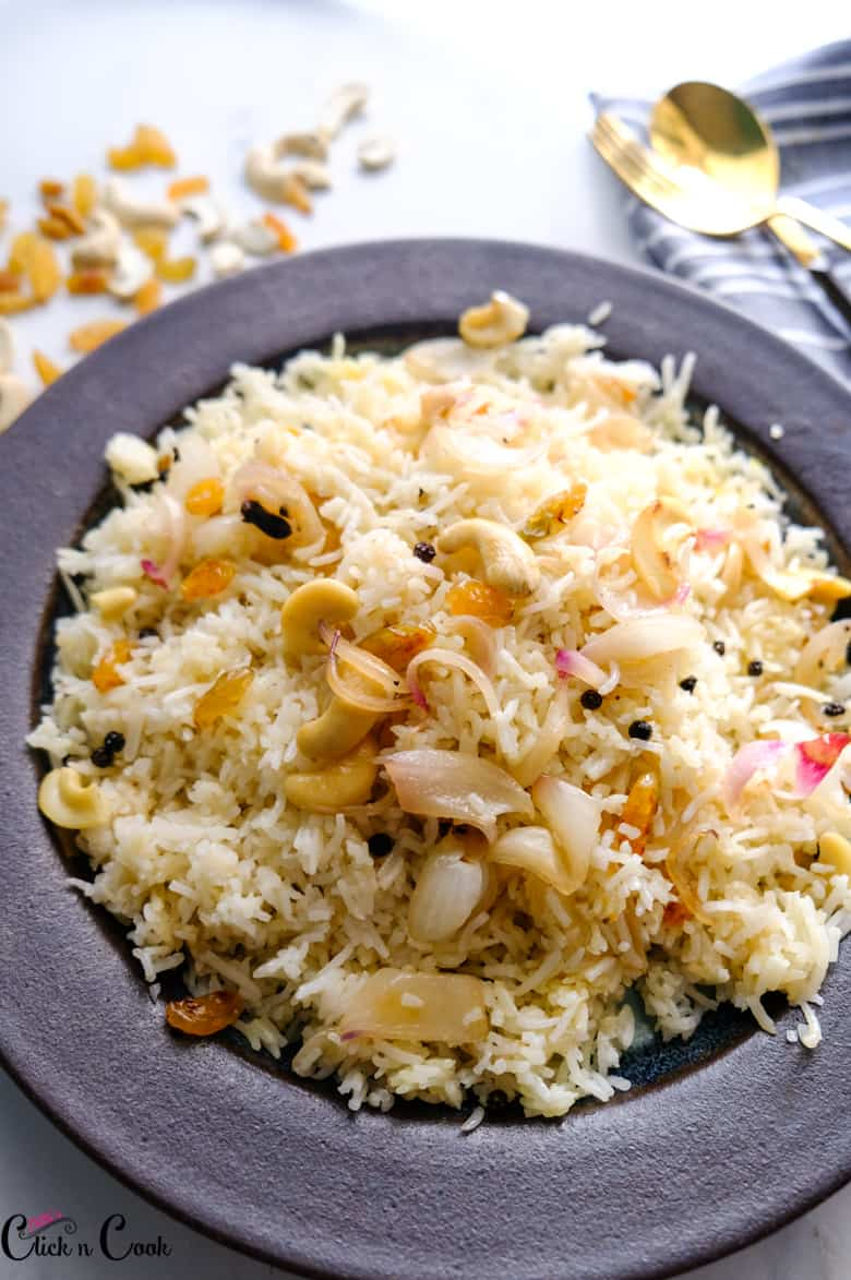 ghee rice recipe is served in plate with fried cashews and raisins on top