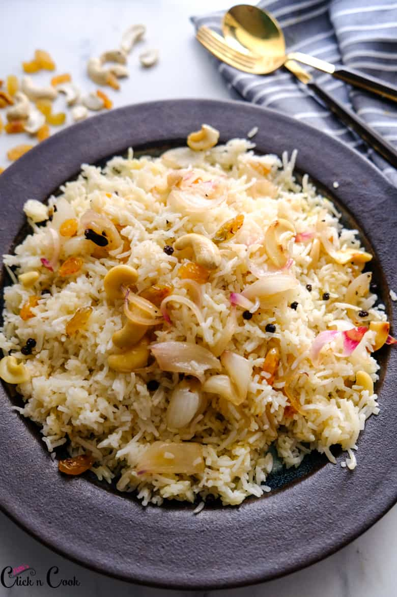 ghee rice is served in plate with spoon and fork aside.