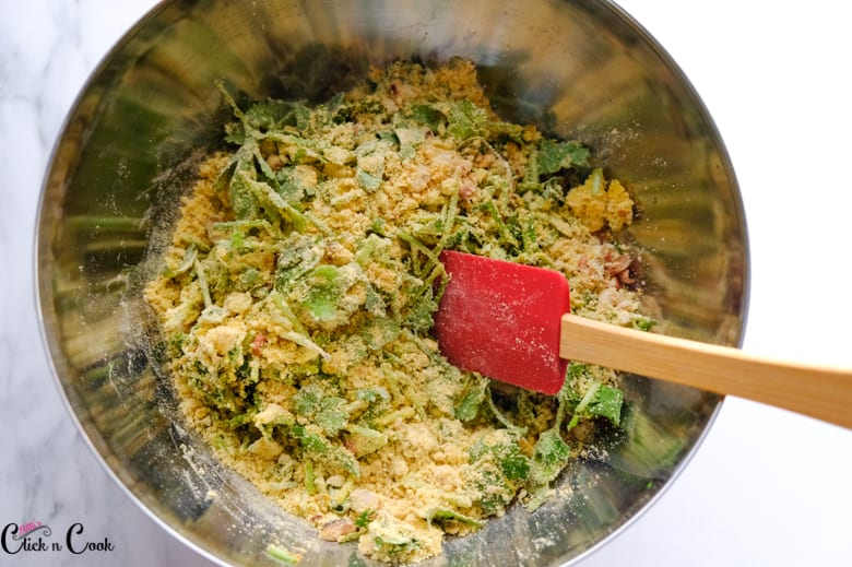 gram flour and coriander leaves are being mixed in spatula