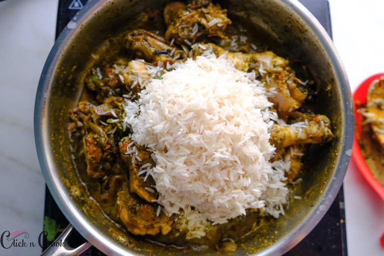 rice is being added to chicken in saute pan