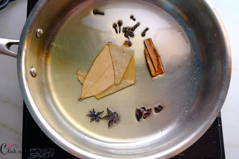 spices like cinnamon, cloves, bay leaf are in saute pan in oil