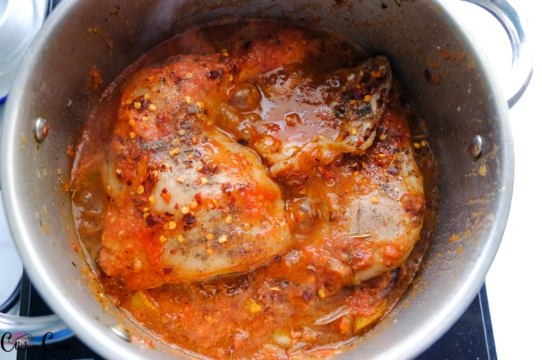 chicken is being cooked in tomato sauce and spices are being sprinkled