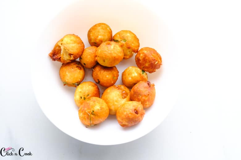 deep fried cottage cheese balls are in white bowl
