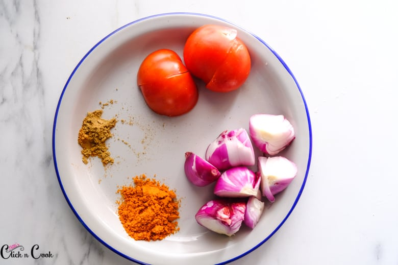a plate of tomato, onion and spices are in plate