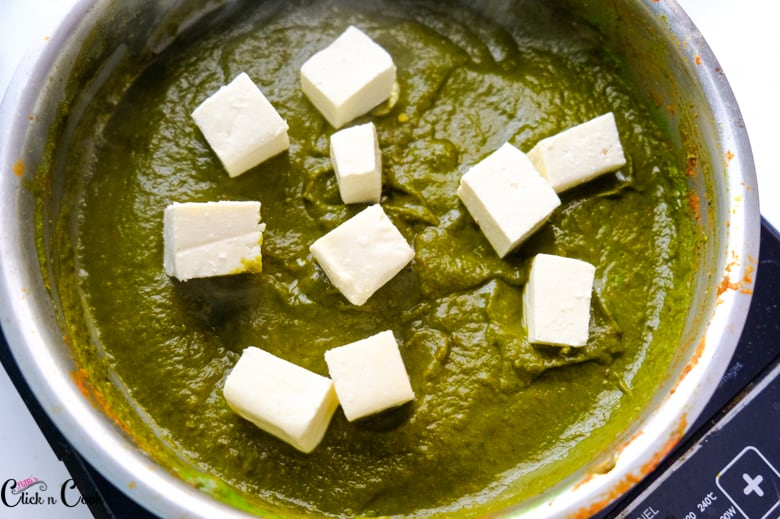 cottage cheese is being added to spinach gravy