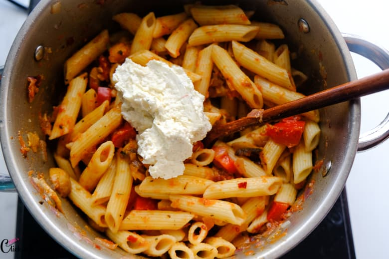 ricotta cheese is being added to pasta in deep pot