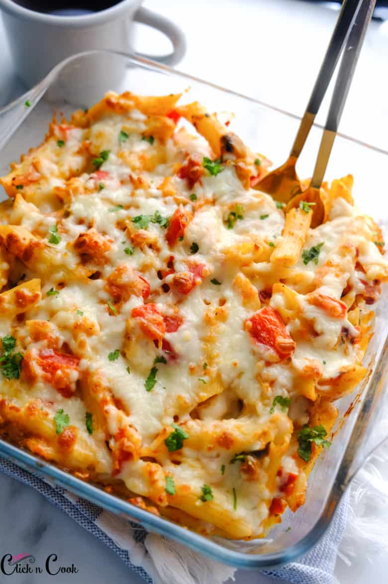Vegetarian baked ziti served in glass baking tray with spoons inside with mug aside.
