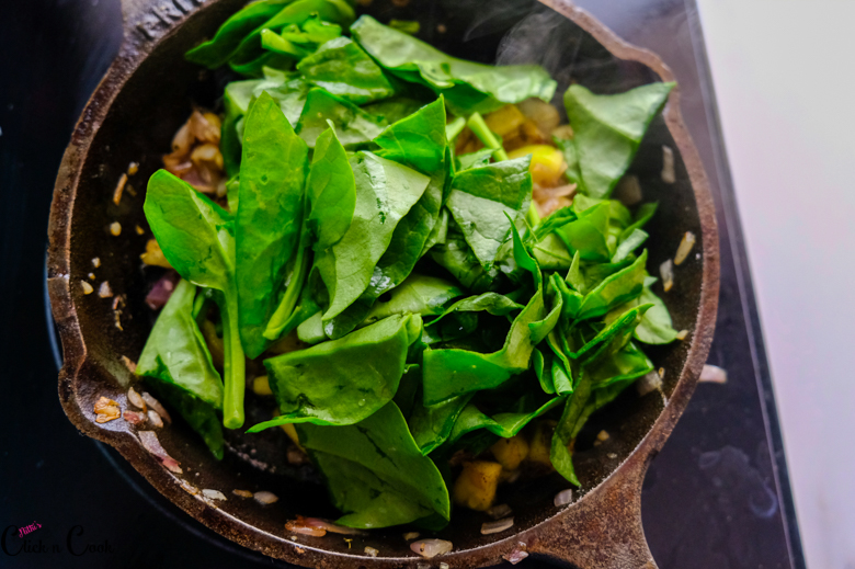 Chopped spinach leaves are being added to cast iron pan