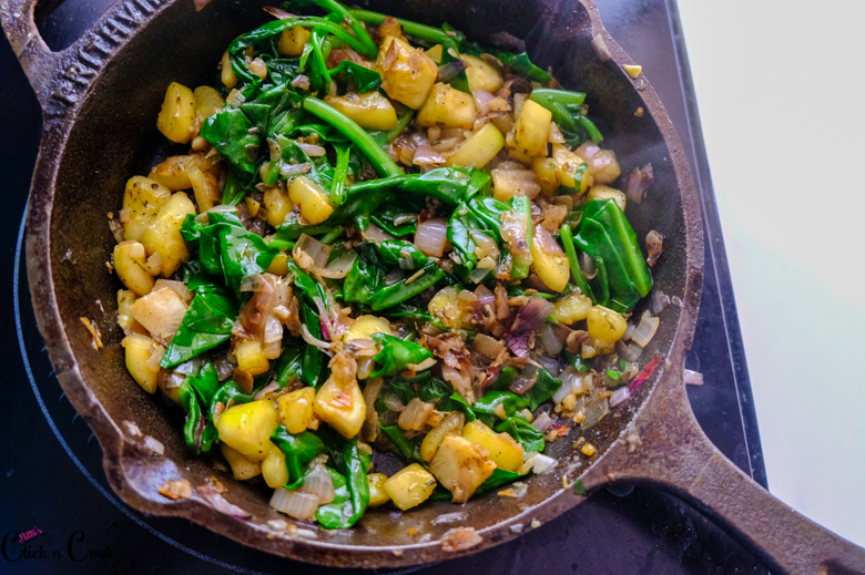 diced zucchini, spinach leaves and onions are in cast iron pan