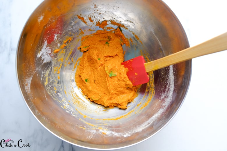 Spice paste is being mixed using spatula in mixing bowl