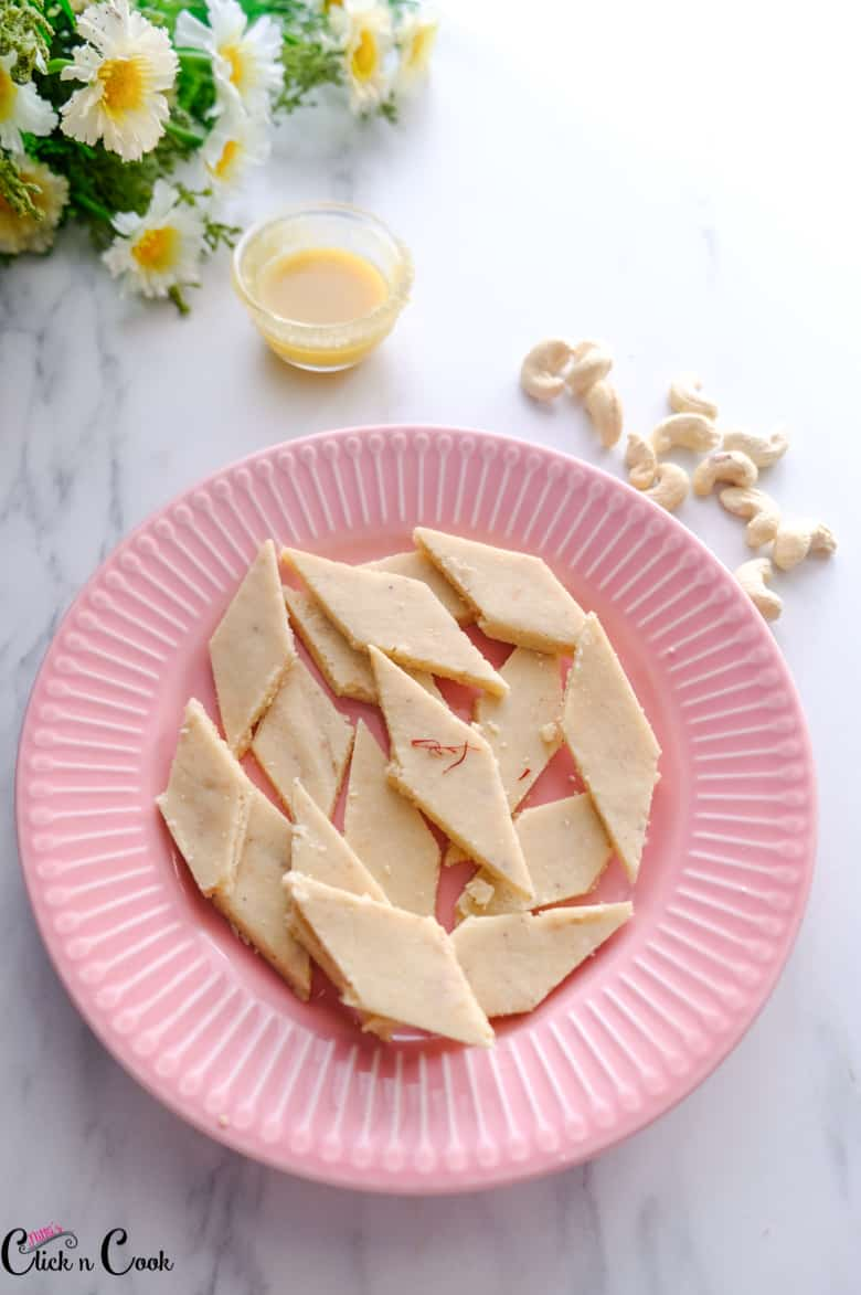 kaju katli served in pink plate with small glass cup of ghee and cashews aside.