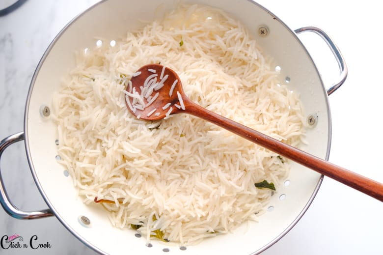 rice is in white colander and wooden spoon is kept over the colander