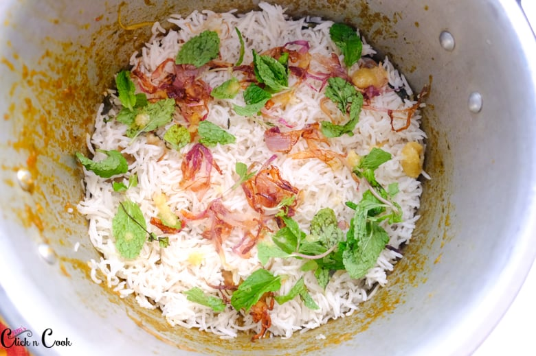 over the cooked rice, mint leaves, onion are sprinkled