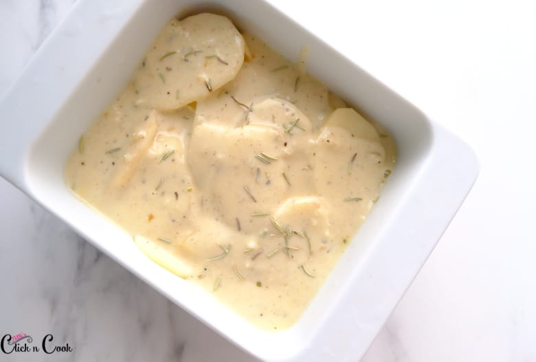 sliced potato with white sauce immersed in white baking ceramic tray