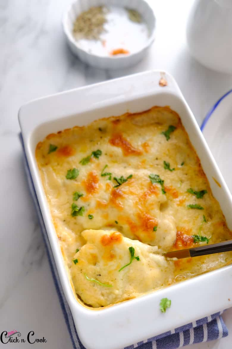 scalloped potatoes recipe served in white baking tray is being taken using spoon