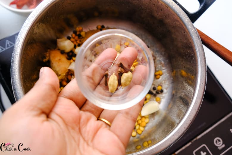 cardamom, cloves in small glass bowl is being added to deep pot