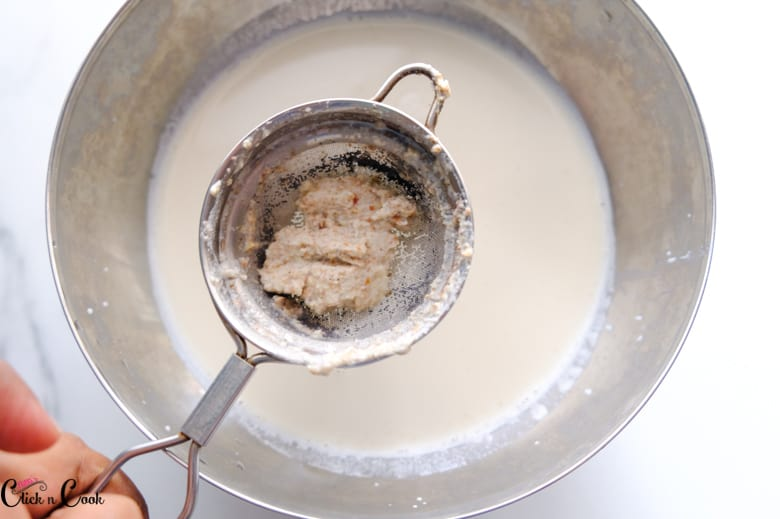 thandai mixture is being filtered using mesh