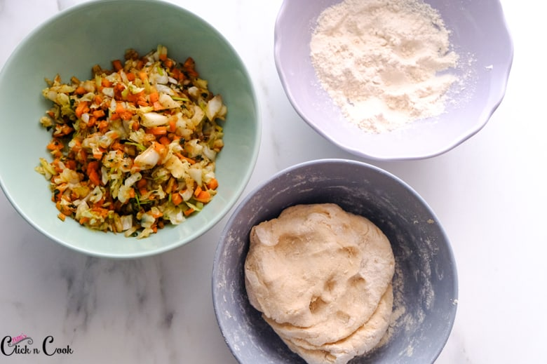 chopped veggies, dough and flour in a bowl
