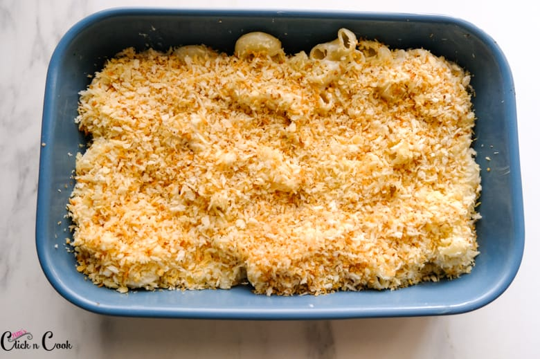 panko breadcrumbs are being added to mac and cheese in blue baking disj