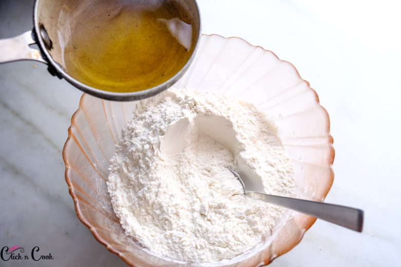 ghee from a small sauce pan is being added to flour in a mixing bowl