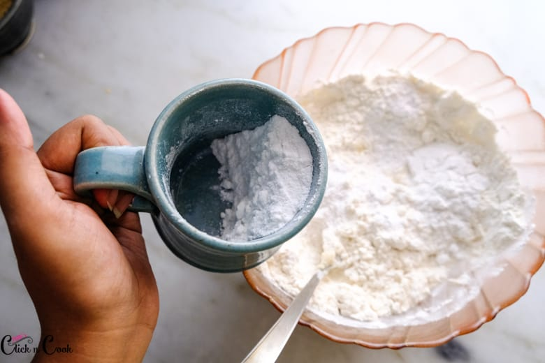 sugar from a blue mug is being added to glass mixing bowl