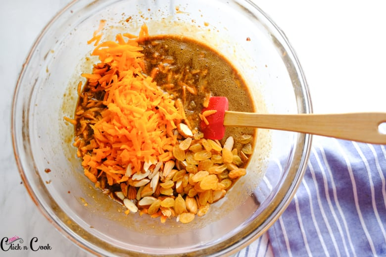 grated carrots and chopped almonds are in glass mixing bowl along with sugar mixture