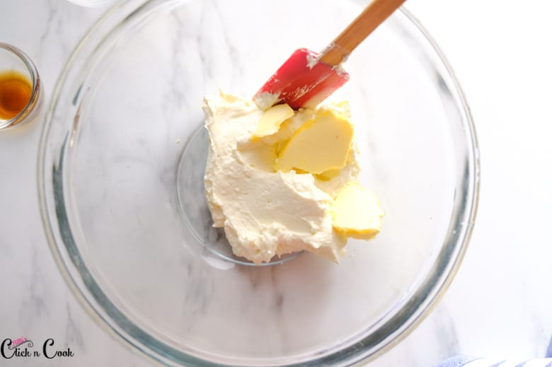 cream cheese and butter in glass mixing bowl with red spatula