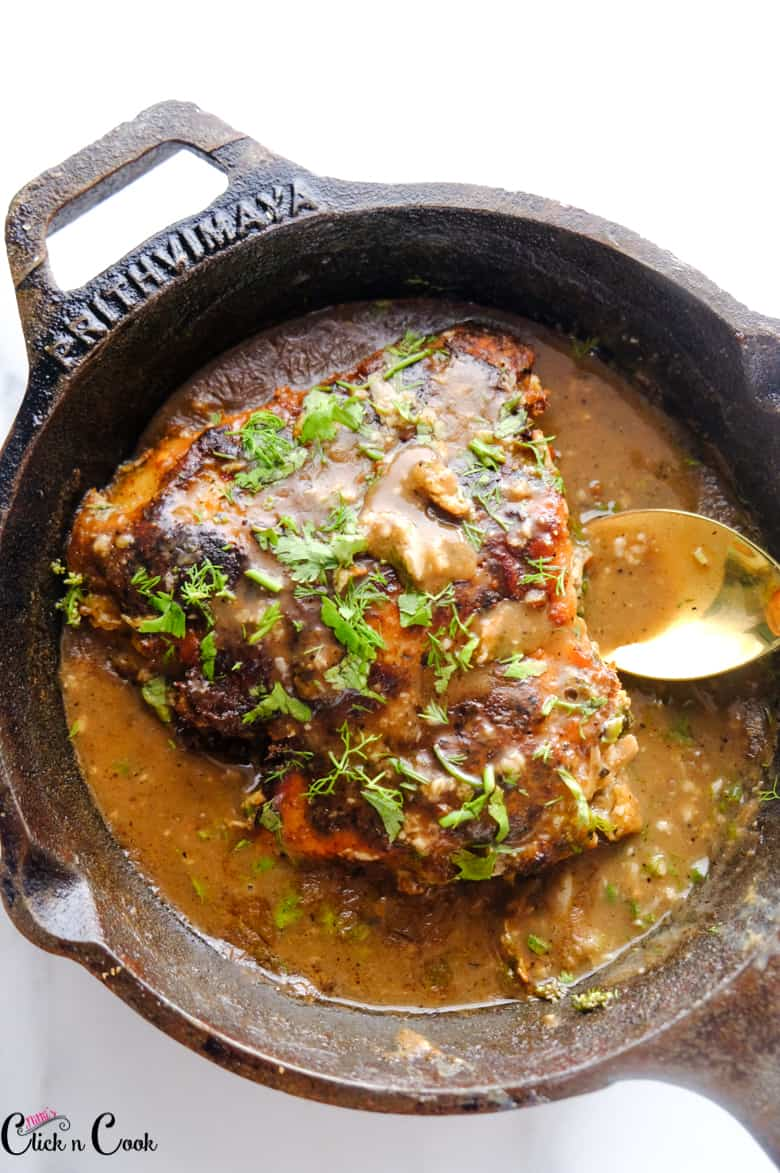 chicken francese in cast iron pan with spoon in