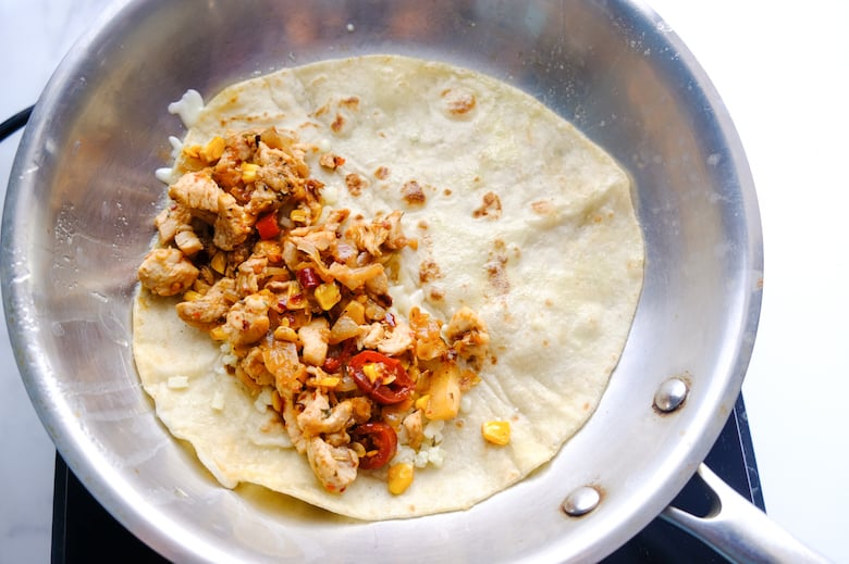 chicken filling is placed on the one side of the tortilla