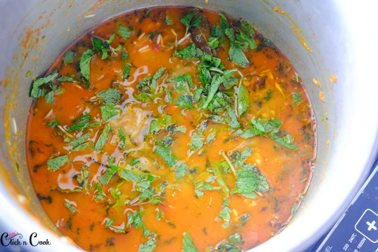 water and rice in deep pot with sprinkles of minty leaves to make shrimp biryani