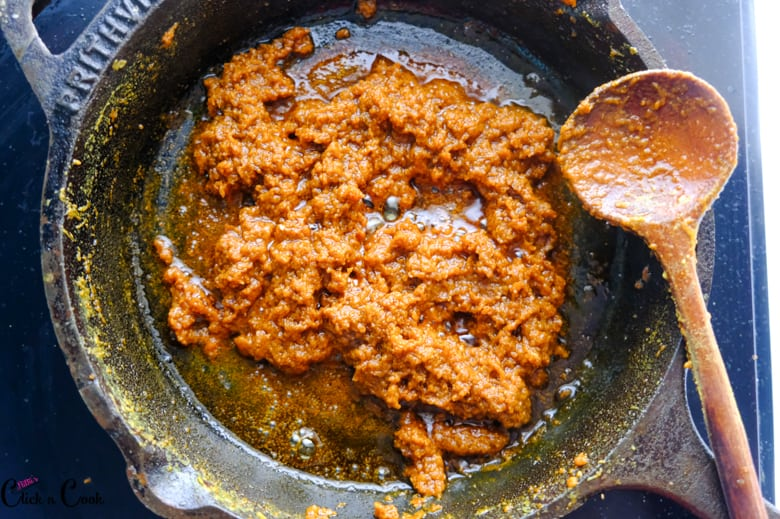 masala is cooked to thicken in cast iron pan