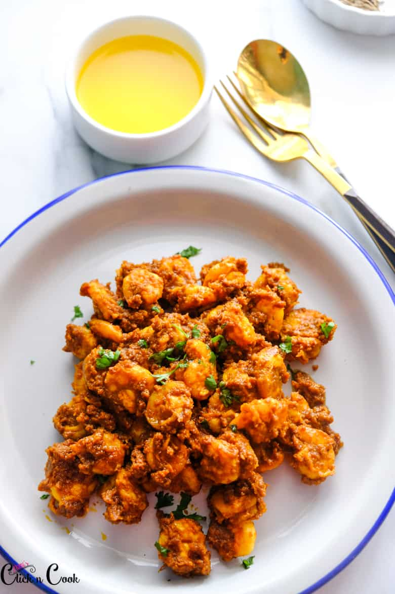 prawn ghee roast served in the plate with spoon aside.