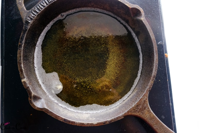 oil is heated up in cast iron pan