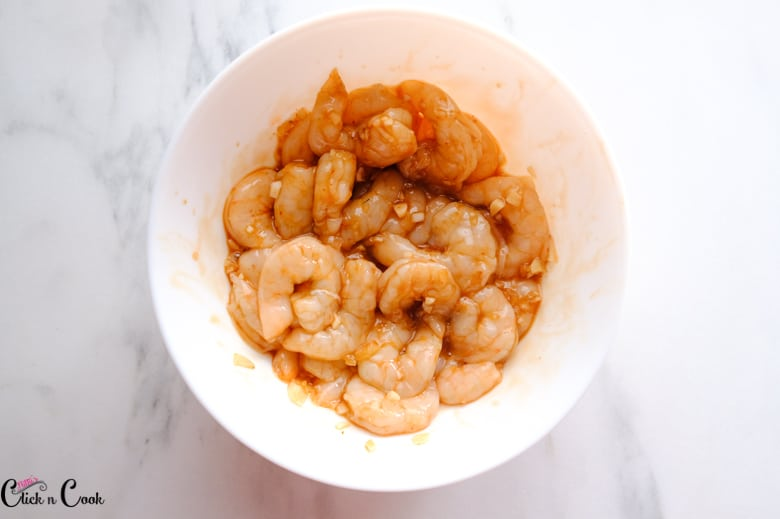 shrimps are marinated in white bowl