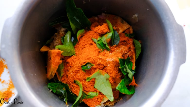 chilli powder and curry leaves are in deep pot