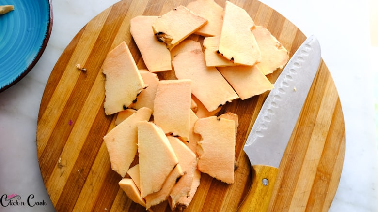 sliced yam in wooden board with knife aside