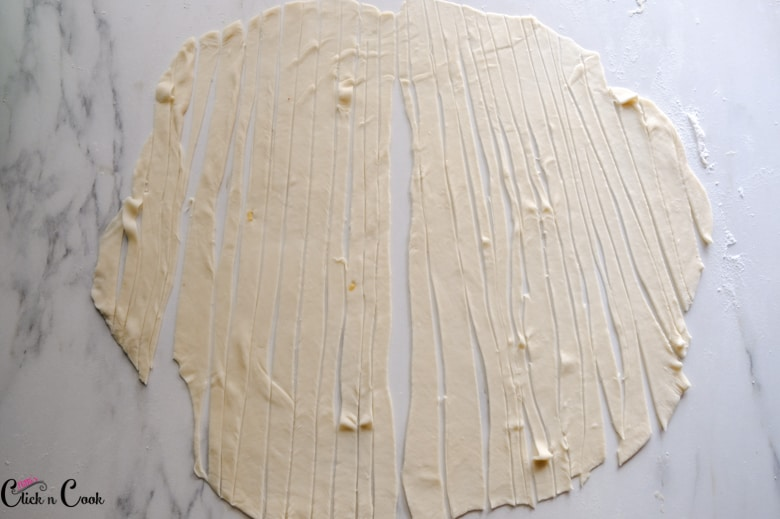 dough is being thinly sliced kept on the white surface