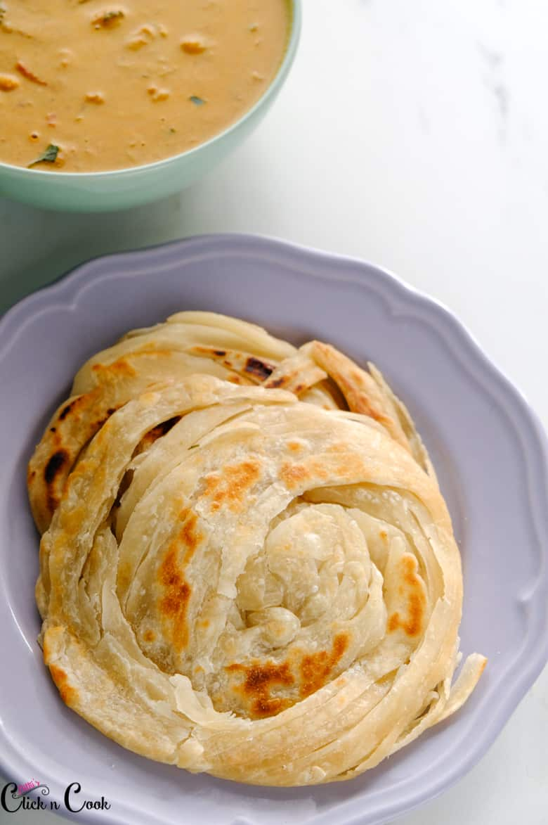 lachha paratha served in grey plate with bowl of curry aside