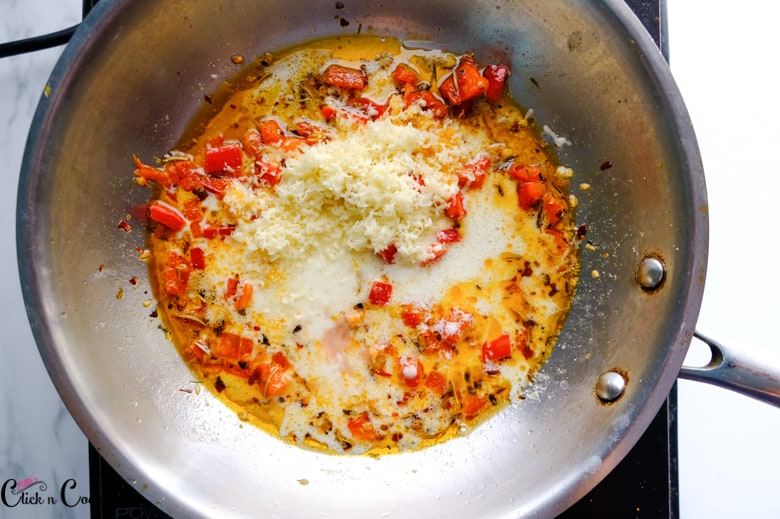 cream, parmesan cheese and red bell pepper is in pan