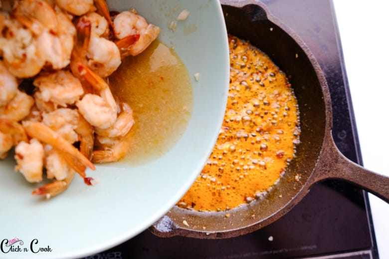 prawns from the bowl is being added to skillet